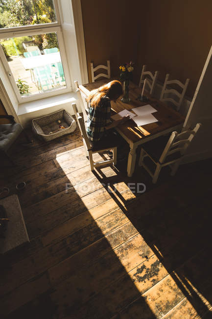 Woman writing on a paper at home — Stock Photo