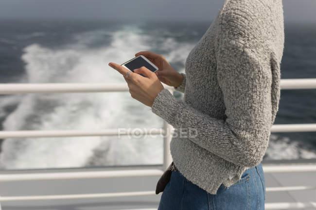 Media sezione di donna che utilizza il telefono cellulare sulla nave da crociera — Foto stock