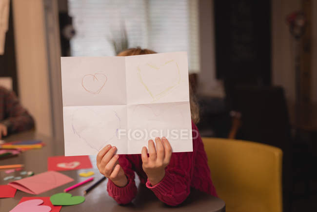 Girl showing drawing paper at home — Stock Photo