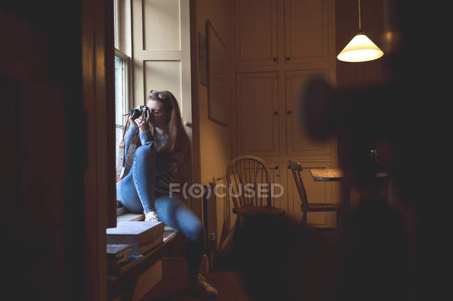 Woman taking picture with retro camera near window at home — Stock Photo