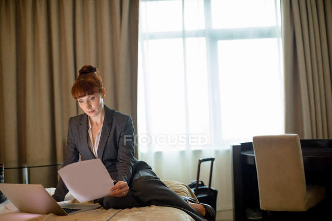 Businesswoman looking at documents on a bed in hotel room — Stock Photo