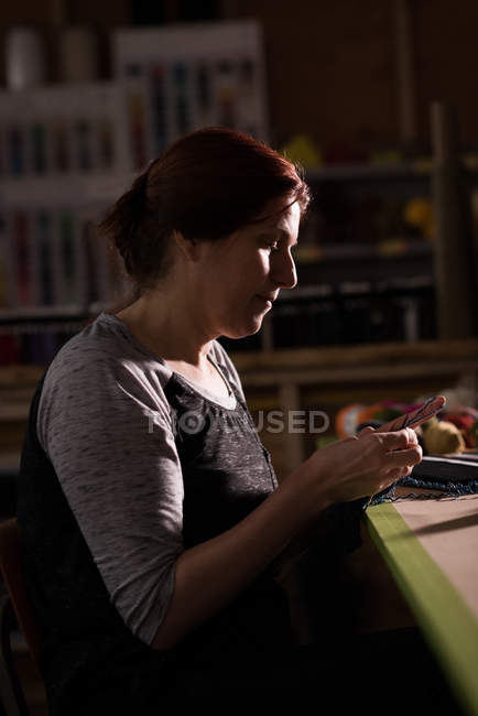 Side view of woman knitting wool at tailor shop — Stock Photo