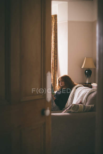 Woman reading a book in living room — Stock Photo