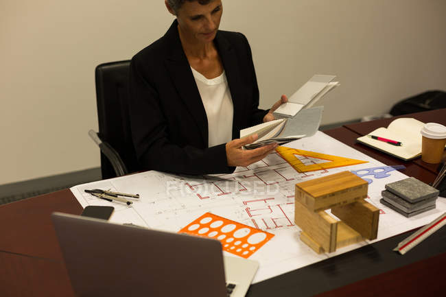 Mulher de negócios maduro verificando documento na mesa no escritório — Fotografia de Stock
