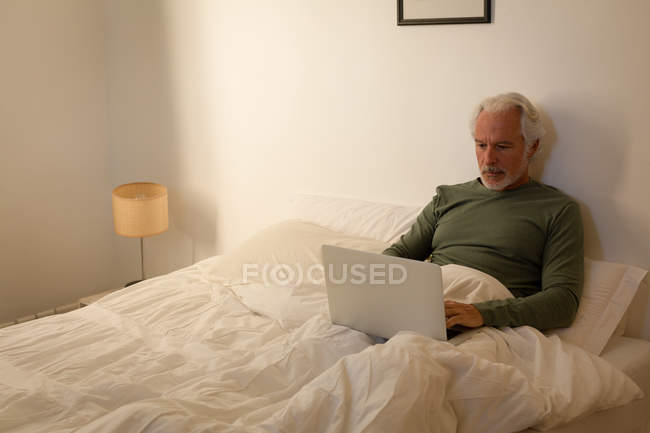 Active senior man using laptop in bedroom at home — Stock Photo