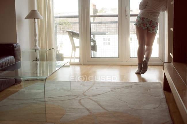 Обрезанный вид женщины, стоящей в солнечном свете в интерьере гостиной . — стоковое фото