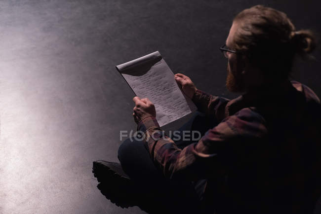 Male actor reading script on stage at theatre  — one person