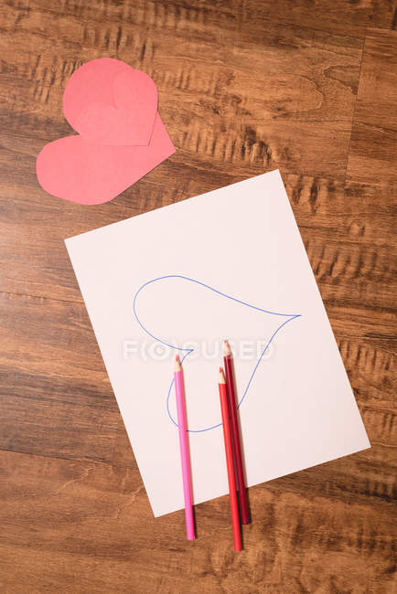 Close-up of heart shape craft and colored pencil on wooden floor — Stock Photo