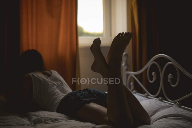 Rear view of woman lying on bed at home — Stock Photo