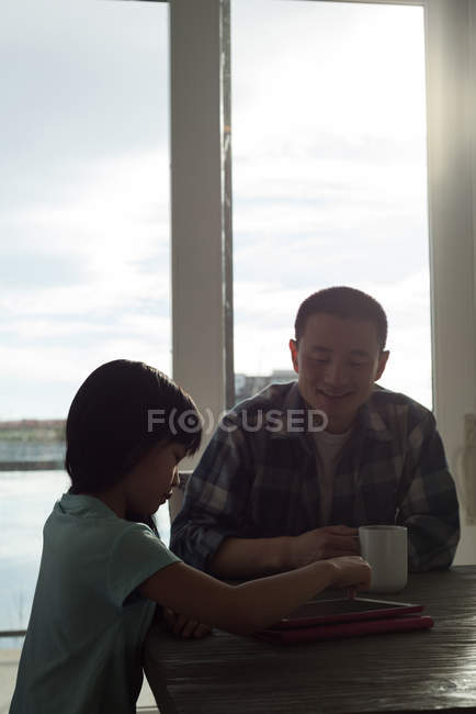 Girl using digital tablet with her father at home — Stock Photo