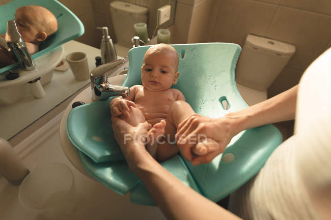 Mother washing a baby in baby bath seat in bathroom sink at home — Stock Photo