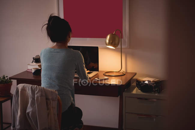 Rear view of woman using laptop in living room at home — Stock Photo