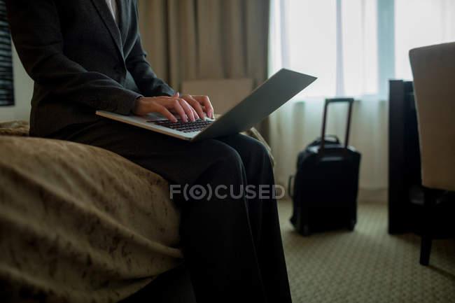 Sezione centrale della donna d'affari che utilizza il computer portatile sul letto in camera d'albergo — Foto stock