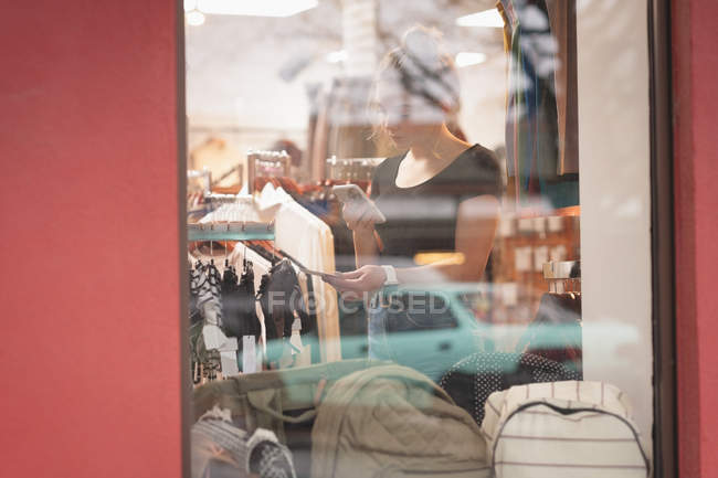 Hermosa chica usando el teléfono móvil durante las compras en el centro comercial - foto de stock