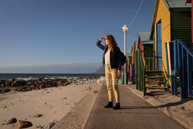 Жінка захисні очі дивлячись на перегляд біля пляжу хатин у sunlight — стокове фото