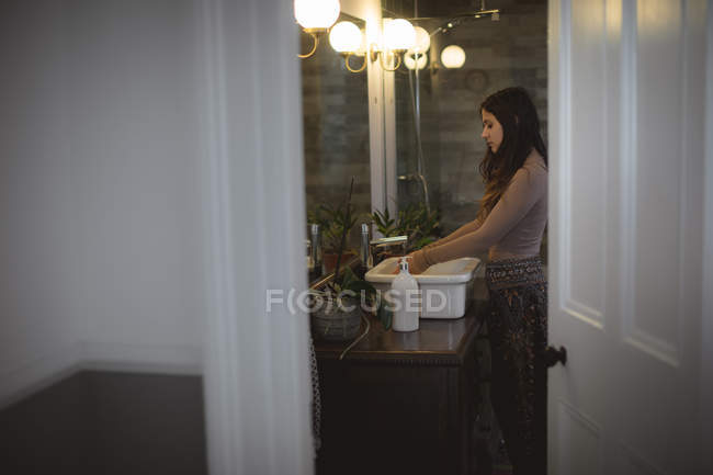 Woman washing her hands in sink at bathroom — Stock Photo