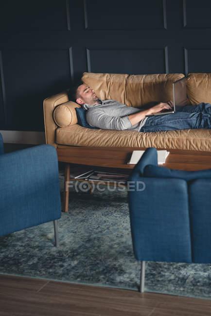 Бизнесмен, использующий ноутбук на диване в офисе — стоковое фото