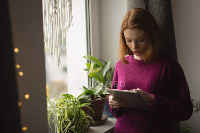 Woman using digital tablet near window at home — Stock Photo