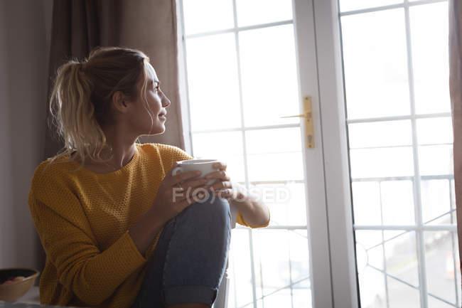 Donna premurosa che prende un caffè a casa — Foto stock