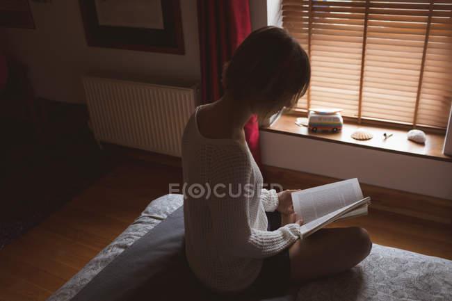 Женщина читает книгу на кровати в спальне дома — стоковое фото