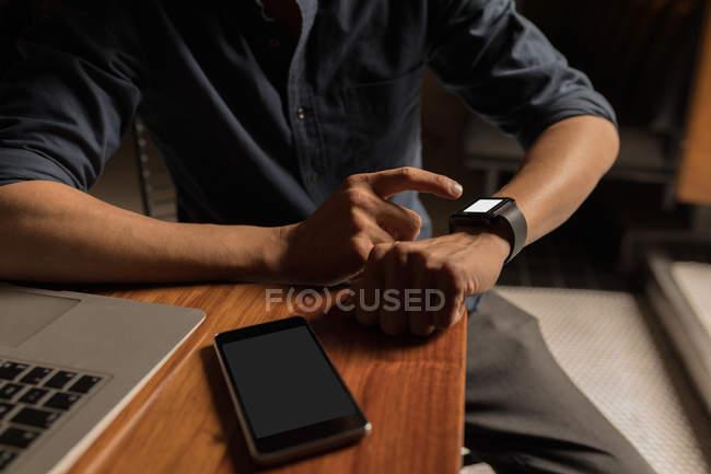 Parte centrale dell'uomo con smartwatch a tavola — Foto stock