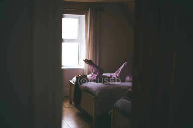 Femme utilisant mobile tout couché sur le lit dans la chambre à coucher à la maison — Photo de stock
