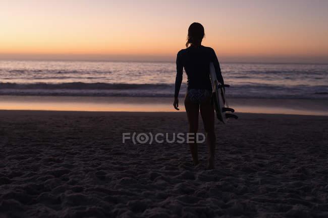 Silueta de mujer en forma sosteniendo tabla de surf en la playa al atardecer . - foto de stock