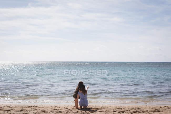 Vue arrière de la mère et de la fille sur la plage pointant et regardant la vue — Photo de stock
