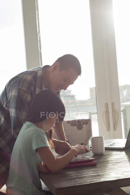 Padre e figlia utilizzando tablet digitale a casa — Foto stock
