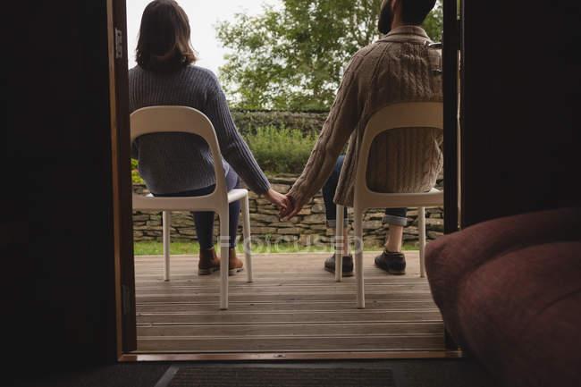 Вид сзади пара, взявшись за руки сидя на стульях — стоковое фото