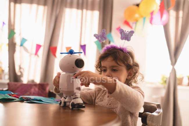 Little girl playing with robot toy in living room at home. — Stock Photo