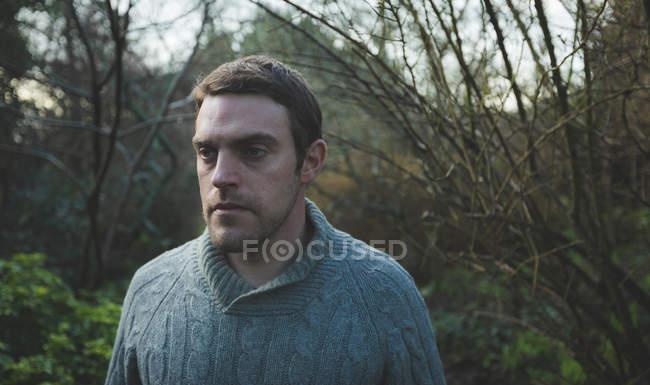 Homme réfléchi debout dans la forêt à la campagne — Photo de stock