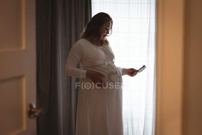 Schwangere betrachtet ihren Sonografiebericht, während sie ihren Bauch berührt — Stockfoto