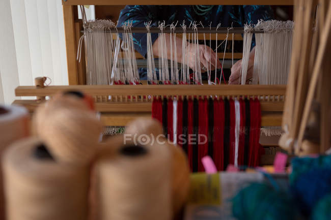 Mid section of senior woman weaving silk at shop — Stock Photo