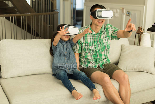 Father and daughter using virtual reality headset at home — Stock Photo