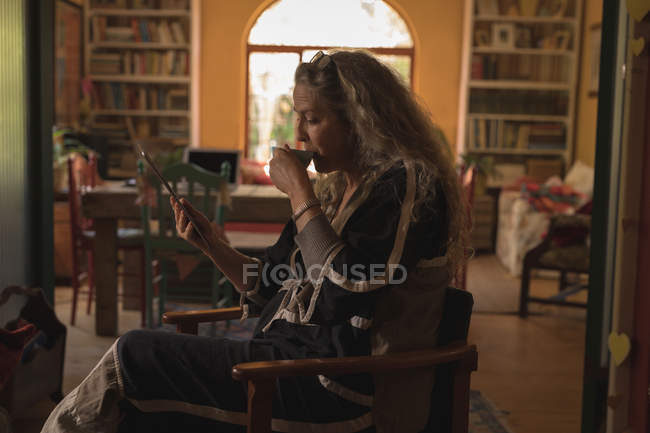 Mature woman using digital tablet while drinking coffee at home — Stock Photo