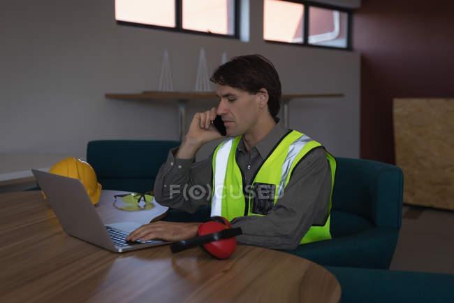 Männlicher Arbeitnehmer telefoniert am Schreibtisch im Büro — Stockfoto