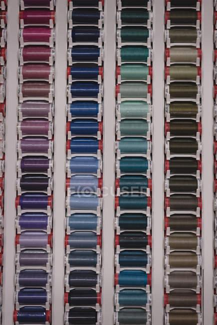 Hilos multicolores dispuestos en fila en sastrería - foto de stock