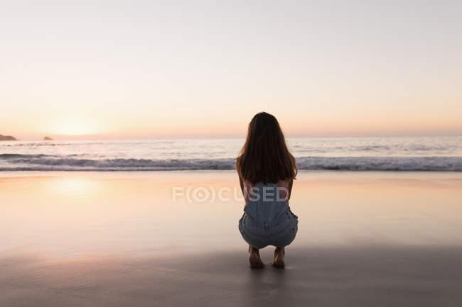 Frau kauert in der Abenddämmerung am Sandstrand. — Stockfoto