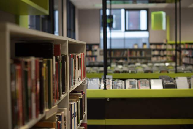 Книги на полке в библиотеке — стоковое фото
