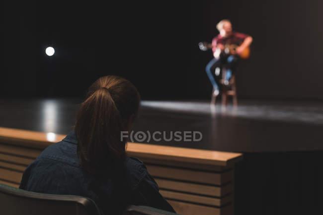 Женщины смотрят музыкант играл на гитаре на сцене в театре. — стоковое фото