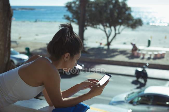 Vista lateral da mulher usando telefone celular em casa na frente da janela — Fotografia de Stock