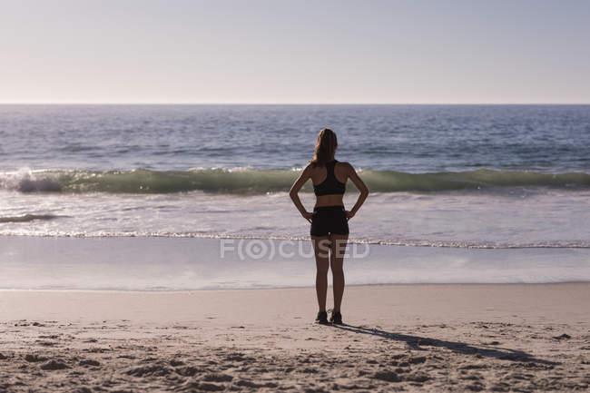 Apta mulher em pé com as mãos nos quadris na praia no entardecer, traseira vista — Fotografia de Stock