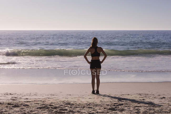 Fit woman standing with hands on hips in beach at dusk, rear view. — Stock Photo