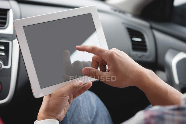 Close-up of male hands using digital tablet in car — Stock Photo