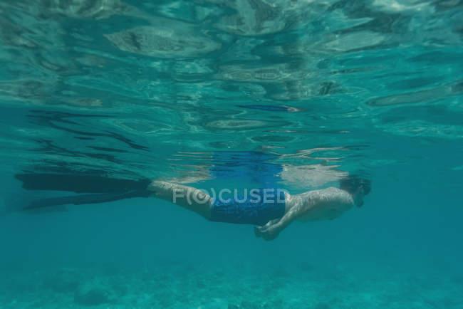 Homme plongée sous-marine dans l'eau de mer turquoise — Photo de stock