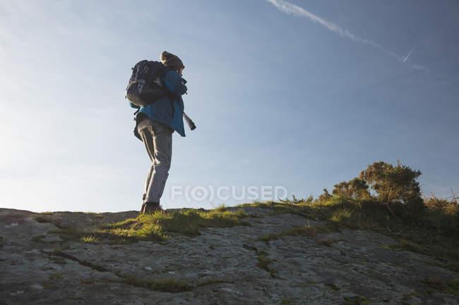 Vista posteriore dell'escursionista maschio in piedi con zaino in campagna — Foto stock