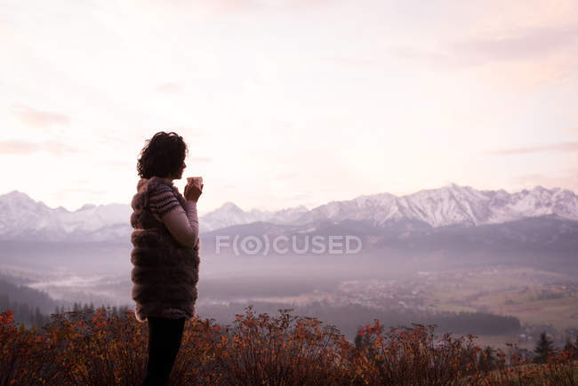 Woman having coffee at countryside during winter — Stock Photo