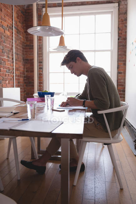 Male executive writing on paper in the creative office — Stock Photo
