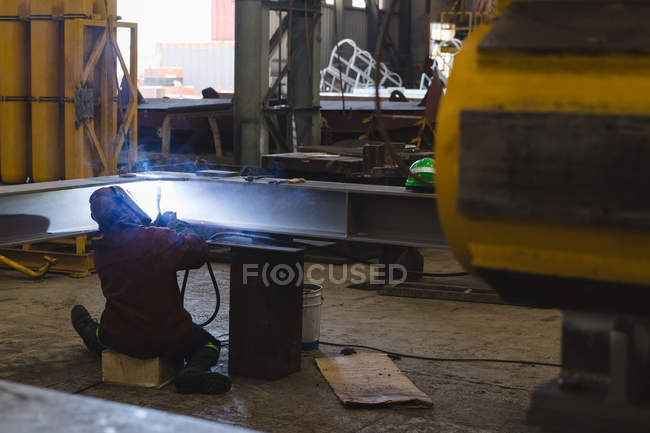 Rear view of welder repairing metal frame in workshop — Stock Photo